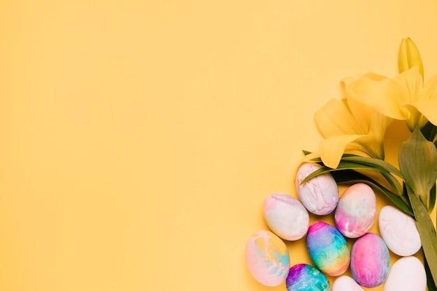 黄色の背景の角にカラフルなイースターエッグと新鮮なユリの花