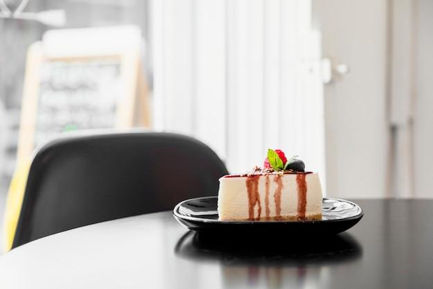 木製のテーブルの上の黒い皿にブルーベリーのチーズケーキ