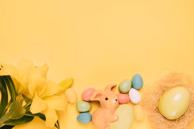 イースターエッグと黄色の背景に巣の美しいユリの花