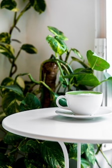 白いテーブルの上のカップに熱いお茶抹茶ラテ