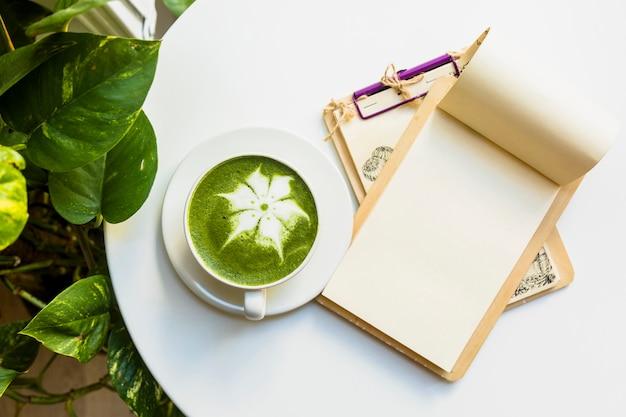 白いテーブルの上のクリップボードと抹茶抹茶ラテカップの俯瞰