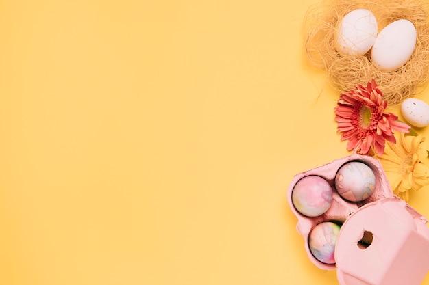 ガーベラの花と黄色の背景にテキストを書くためのコピースペースとカラフルなイースターエッグ