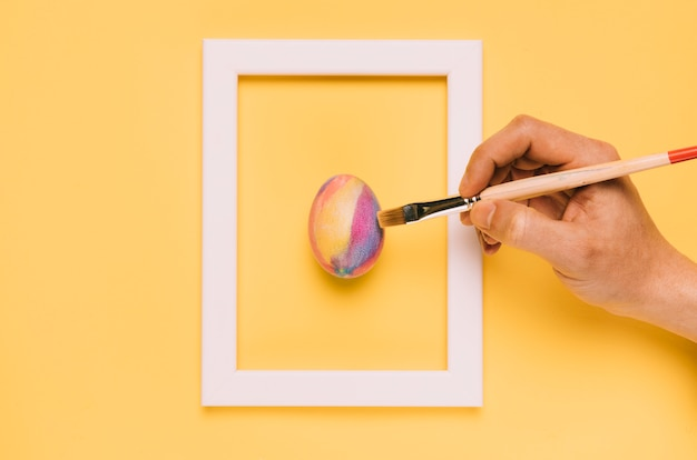 黄色の背景上のフレーム内のブラシでイースターエッグを塗る手のクローズアップ