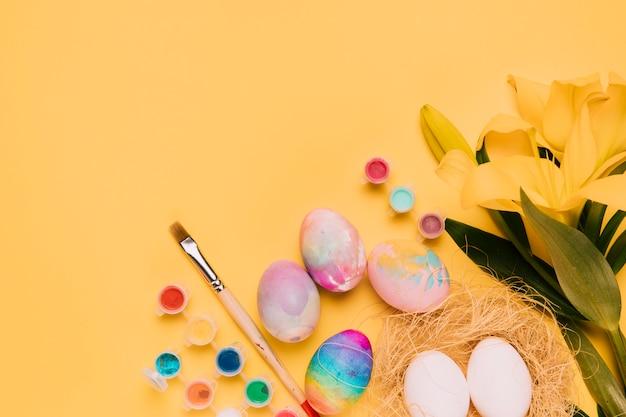 カラフルなイースターエッグと新鮮なユリの花。絵筆と黄色の背景に水彩画