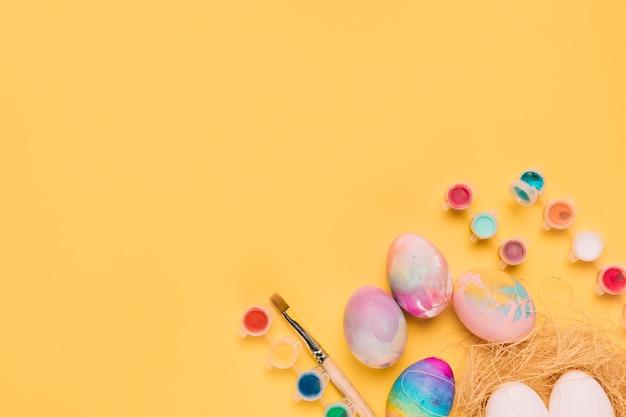 Вид сверху на акварель в пластиковой бутылке; пасхальные яйца на углу желтого фона