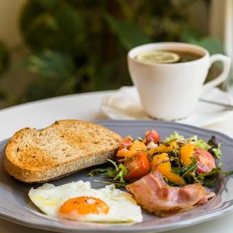 Тост; половину жареного яйца; салат и бекон на серой тарелке возле чайной чашки