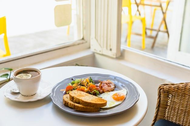 ティーカップ窓の近くのテーブルに健康的な新鮮な朝食