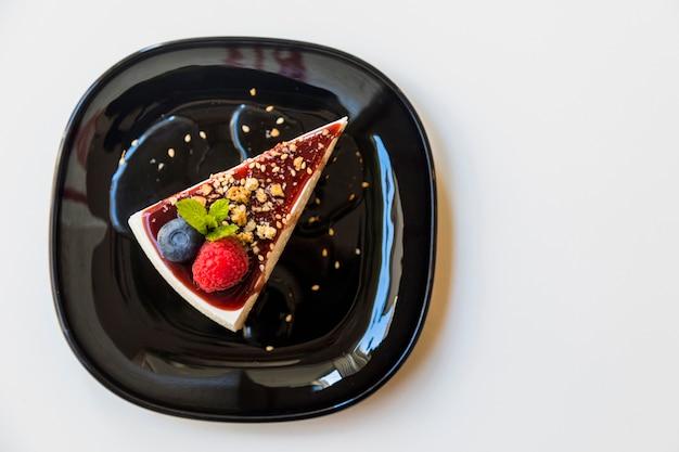 新鮮なラズベリー入りの自家製チーズケーキ。ブルーベリーと白い背景の上の黒い皿にデザートのミント
