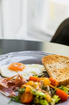 Завтрак серая тарелка с яйцом; бекон; тост и салат на столе