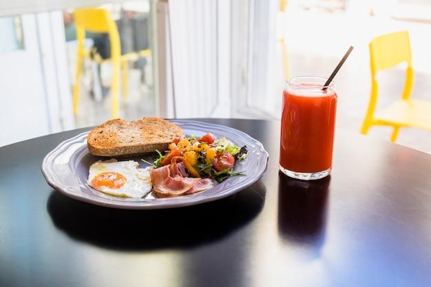 ジュース;黒いテーブルの上の灰色の皿に新鮮な朝食