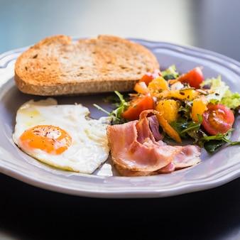 Вкусный тост; половину жареного яйца; бекон и салат на серой тарелке