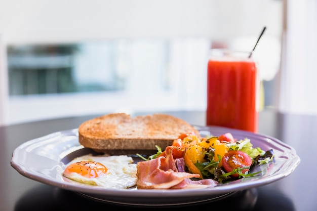 黒いテーブルの上のスムージーとグレーのプレートでの朝食します。