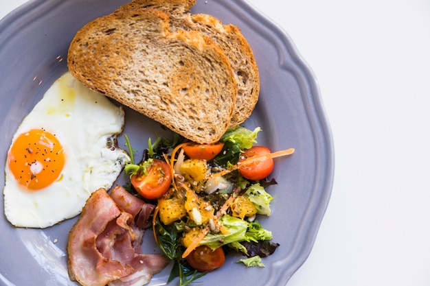 Поднятый вид тоста; жаренное яйцо; бекон; салат на серой тарелке на белом фоне