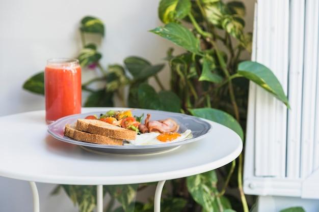 スムージーのグラス。白い丸テーブルの上皿に朝食します。