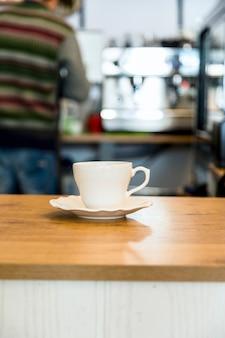 多重カフェテリアの背景の上の木製のテーブルの上のコーヒーカップ