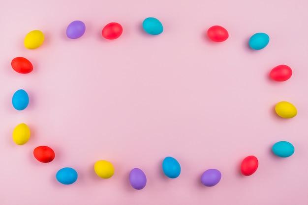 ピンクのテーブルにカラフルなイースターエッグからフレーム