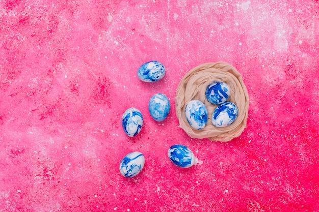 Пасхальные яйца синего цвета в гнезде