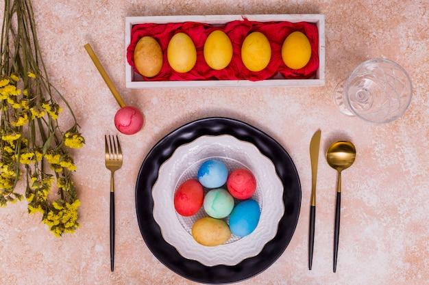 Пасхальные яйца на тарелке с цветами