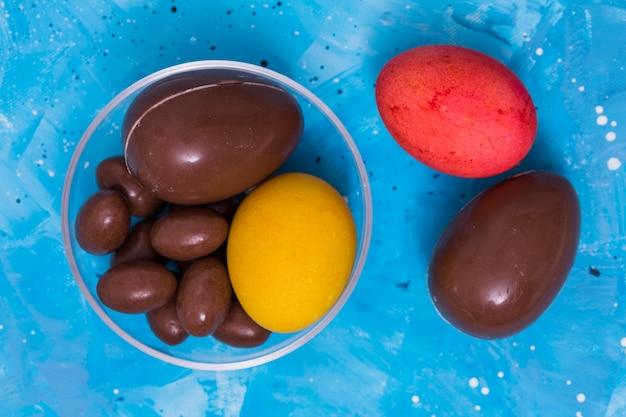 青いテーブルの上のチョコレートとカラフルなイースターエッグ