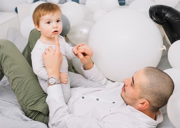 風船の近くのベッドで遊ぶ小さな赤ちゃんを持つ男