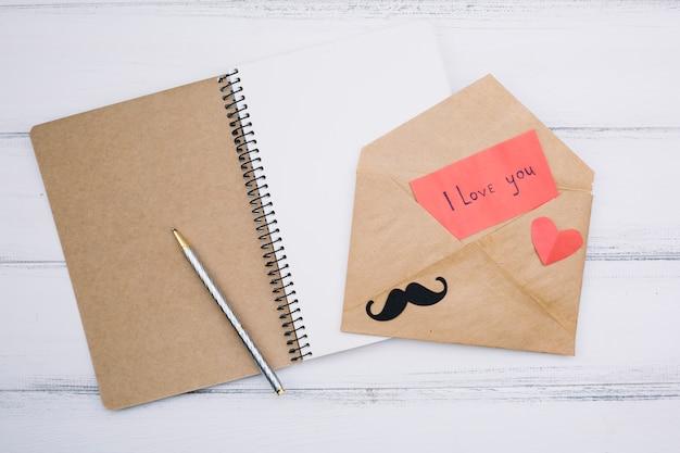Бумага с надписью «я люблю тебя» возле сердца и усы на письме возле блокнота
