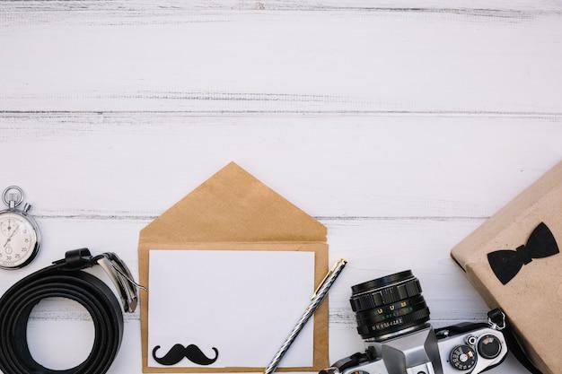 カメラ、箱、ストップウォッチ、革ストラップの近くに紙で封筒
