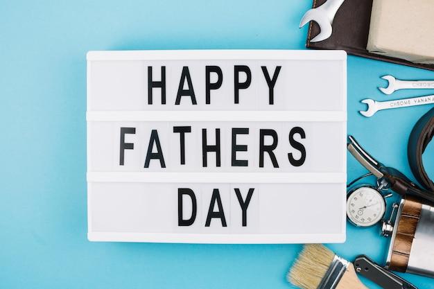 男性のアクセサリーの近くのタブレットで幸せな父親の日タイトル