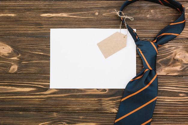 Бумага возле полосатого галстука с биркой