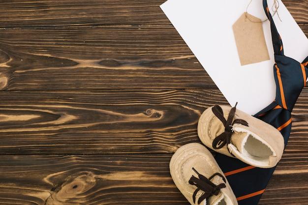 タグと子供の靴と縞模様のネクタイの近くに紙
