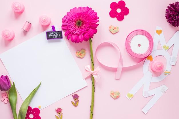 紙とテーブルの上の花を持つママ碑文