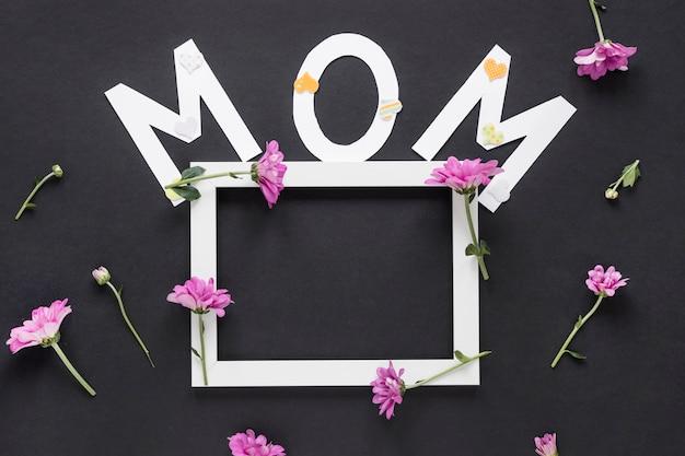 フレームとテーブルの上の花を持つお母さん碑文
