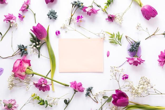 白いテーブルの上の紙とさまざまな花