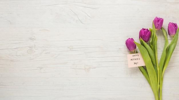テーブルの上の幸せな母の日碑文とチューリップ