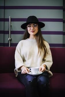 帽子と飲み物のカップと眼鏡のエレガントな若い女性の笑みを浮かべてください。
