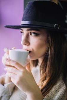 Элегантная молодая женщина в шляпе с кружкой напитка