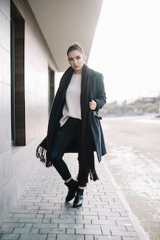 路上でスカーフとコートを着たエレガントな若い女性