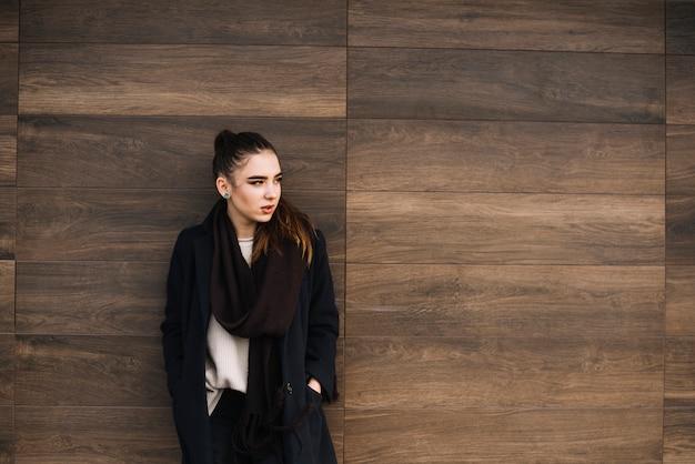 木製の壁の近くのスカーフでコートを着たエレガントな若い女性