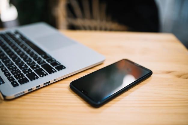 携帯電話と通りのカフェのテーブルでノートパソコン
