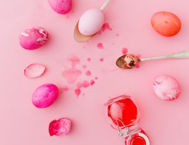 Розовые и красные пасхальные яйца возле ложек и банки с жидкостью для красителей