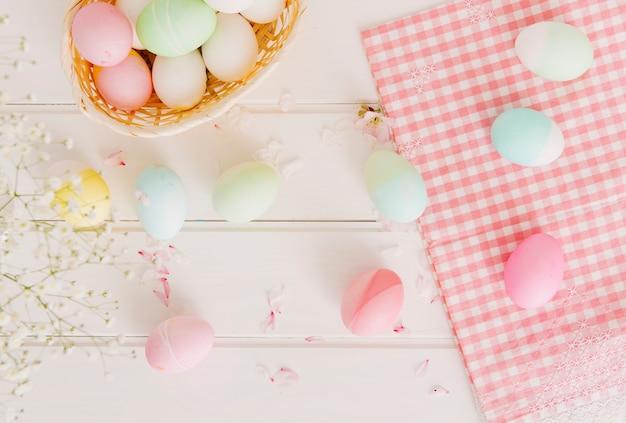 ナプキンとバスケットの近くの花びらの間のイースターエッグのセット