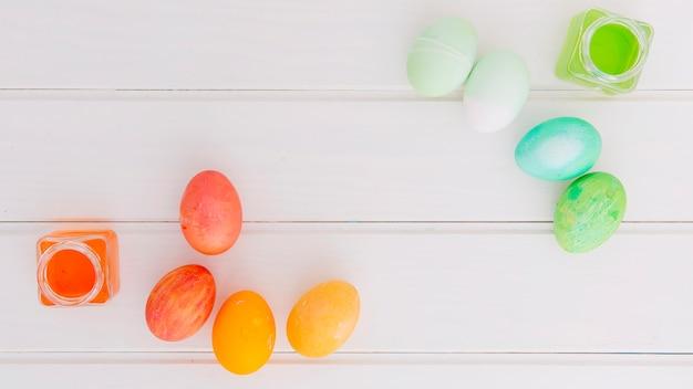 Яркие пасхальные яйца возле банки красителя жидкости на столе