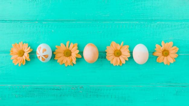 Пасхальные яйца и оранжевые цветы на столе