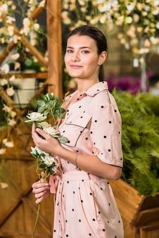 手に白い花で立っている女性