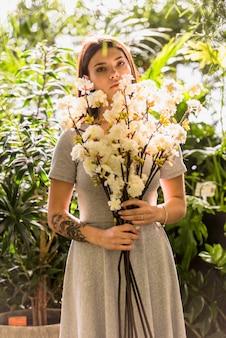 手に白い花で立っている若い女性