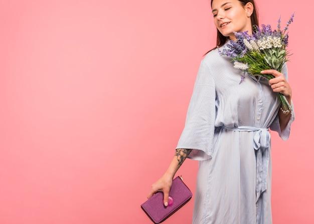 Красивая женщина, стоящая с ярким букетом цветов