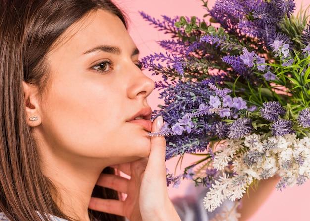 明るい花の花束を持つ思いやりのある女性