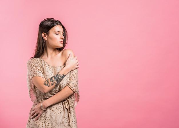 若い女性が裸の肩を持つドレスでポーズ
