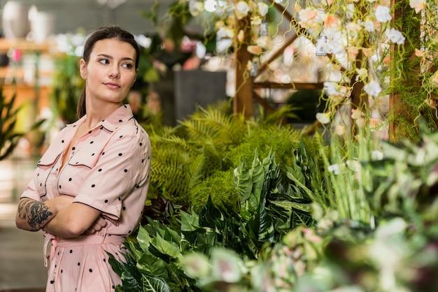 緑の家に立っているドレスの若い女性