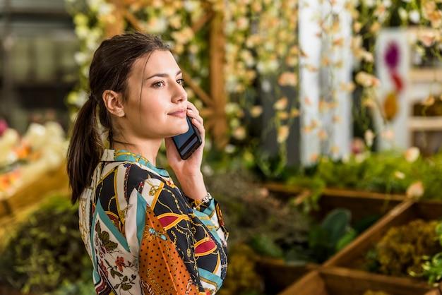 緑の家で電話で話している若い女性