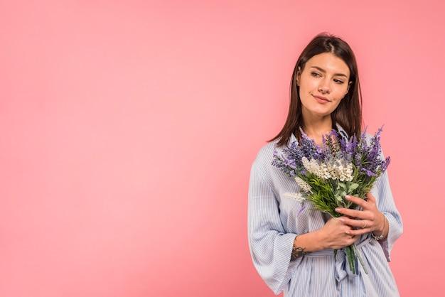 花の束を保持している若い女性